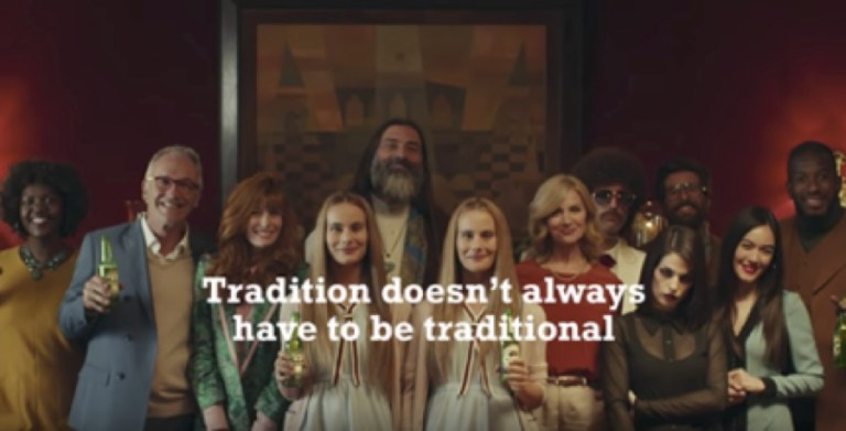 "A dozen people are smiling and holding Heineken beers. Text at the bottom of the image say, ""Tradition doesn't always have to be traditional."""