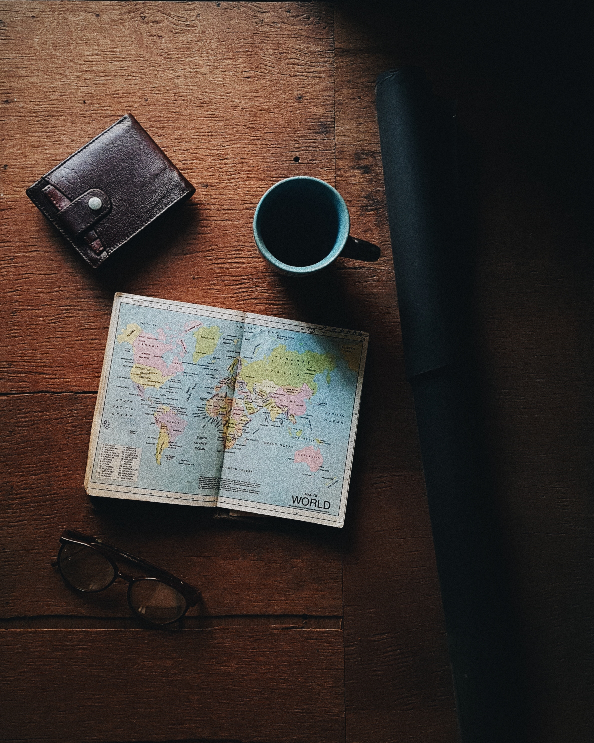 wooden table with a pocket sized world map with coffee mug