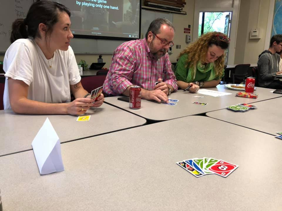 Three people play UNO intensely.