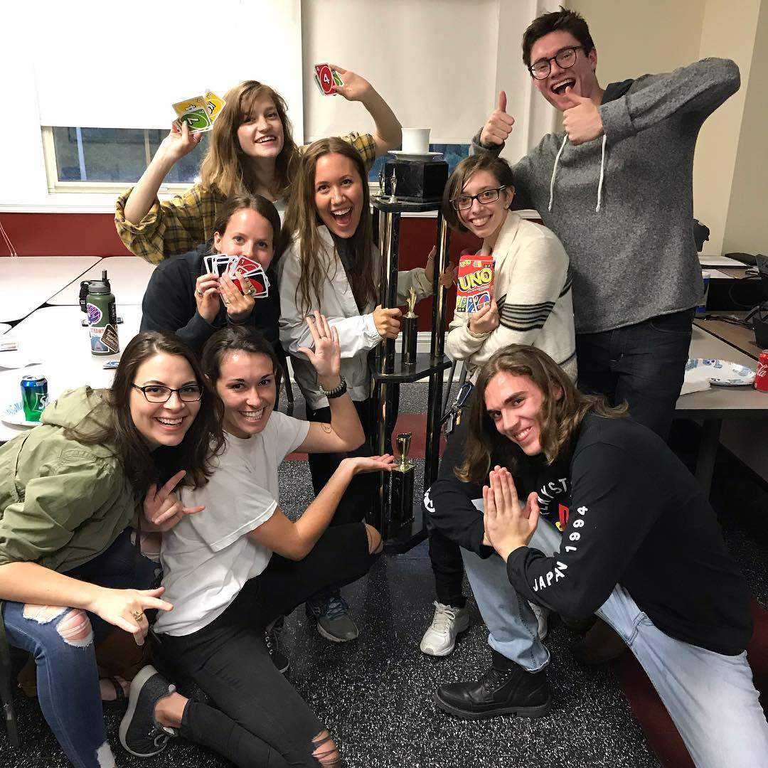Students happy that they won the trophy, showing their Uno cards.