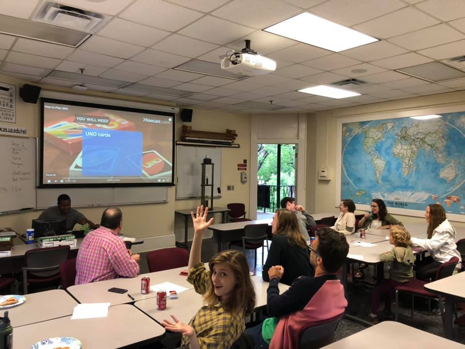 REL students watching an instructional video on how to play Uno. One student is looking back at the camera waving and smiling.