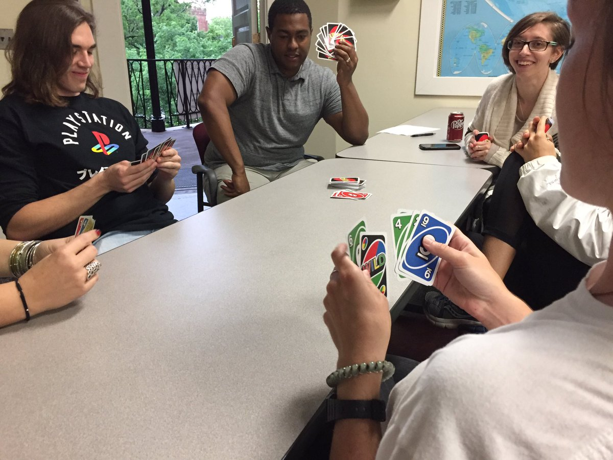 Players looking at their Uno hands before laying cards down.