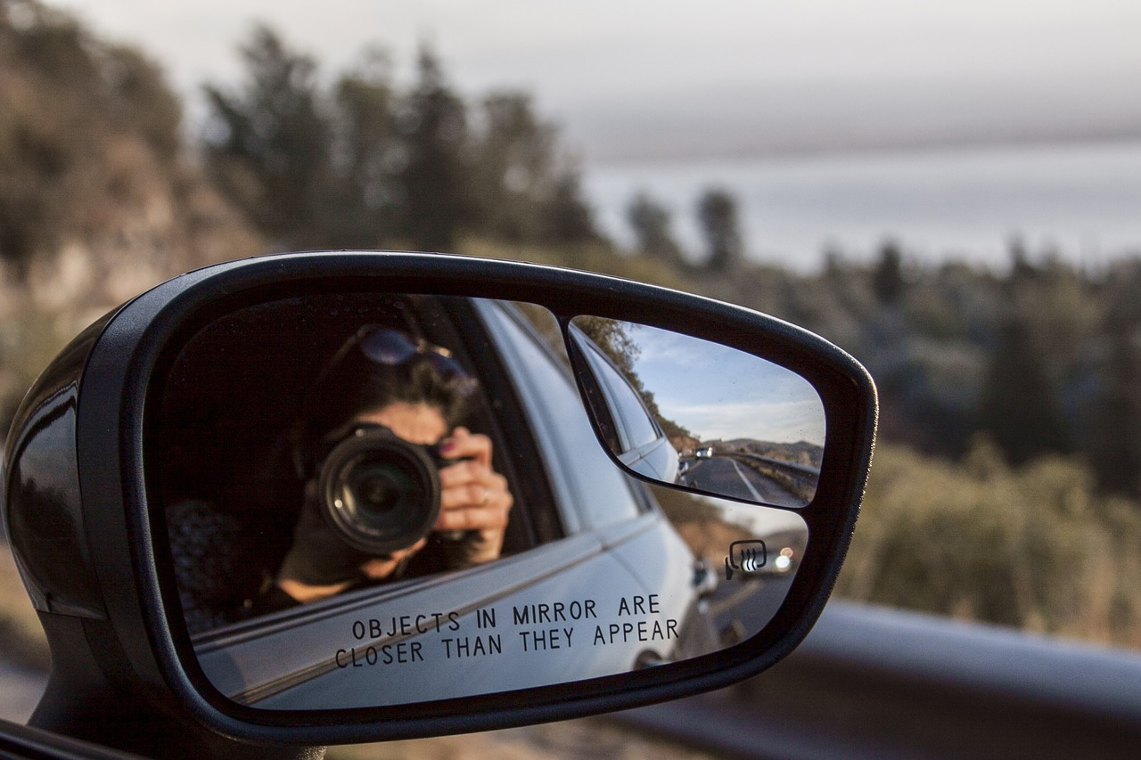 A landscape photo shot from a car driver's camera with a side mirror in view.