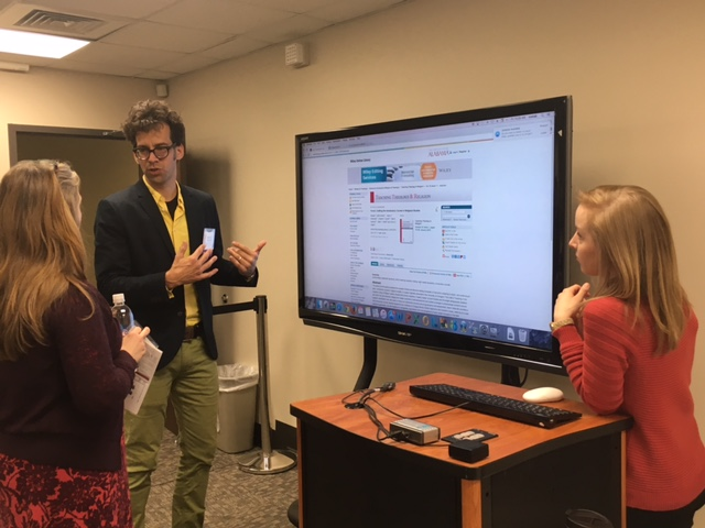 Professor Loewen Presenting to two women with the help of a large digital screen.