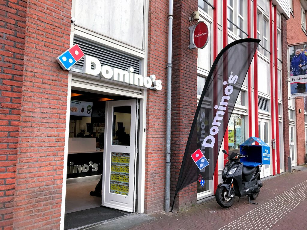 Domino's Pizza restaurant with a delivery bike in front of the store.