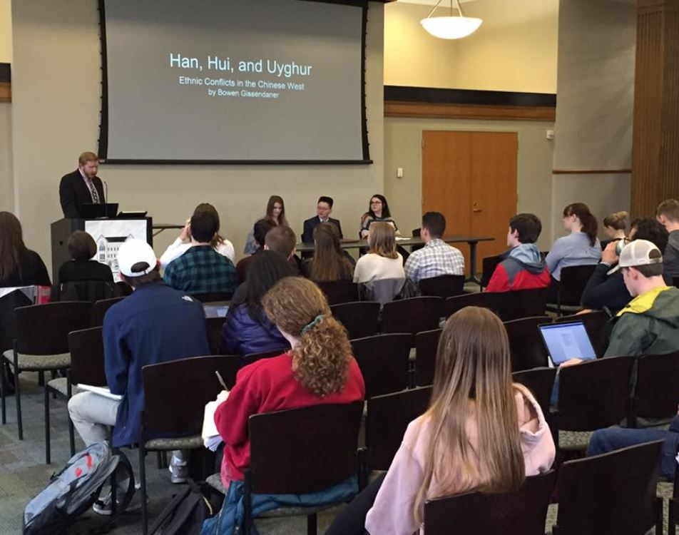 Student presenting a paper at the 2019 undergrad research symppsoium, with students listening