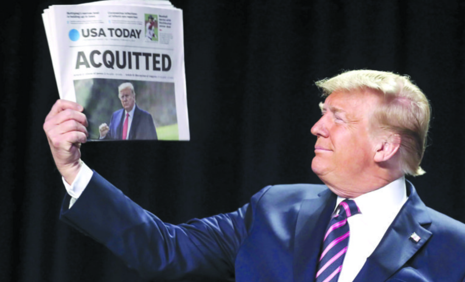 President Trump poses with newspaper headline sayig he was acquited
