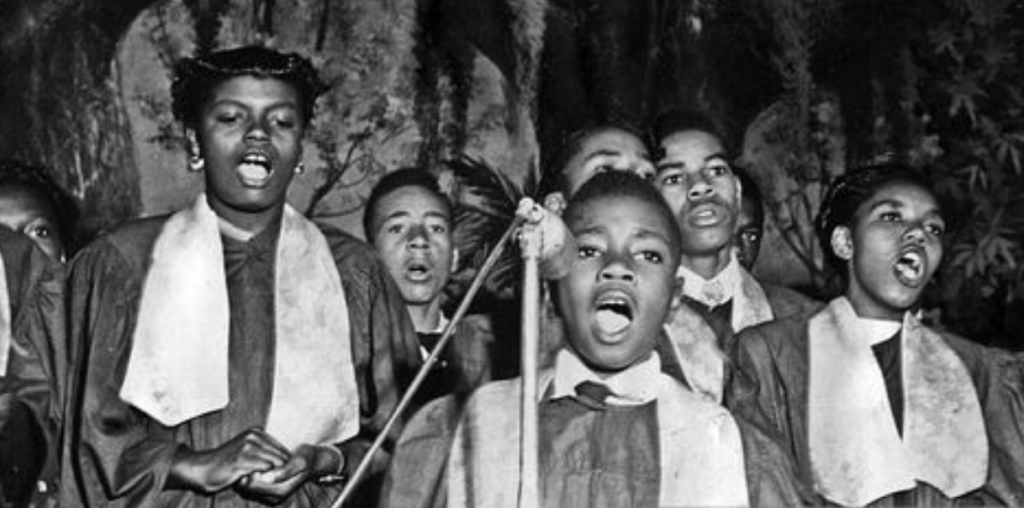 Young African American boy singing as part of a church choir