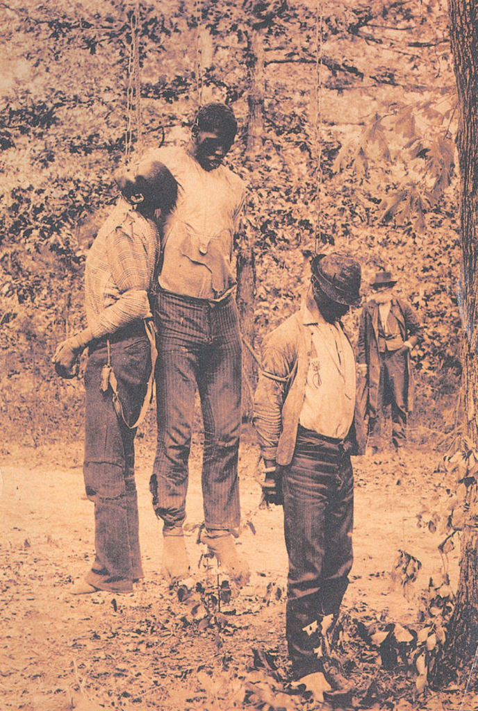 Historical photo of three murdered African Americans who were lynched and haning by chains from a tree.