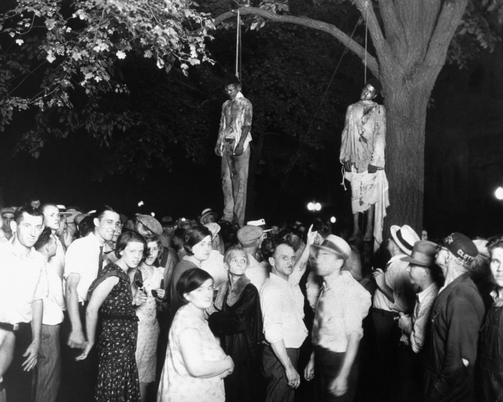 Historical photo of two African Americans lynched from trees with a large crowd of whites gathered to watch.