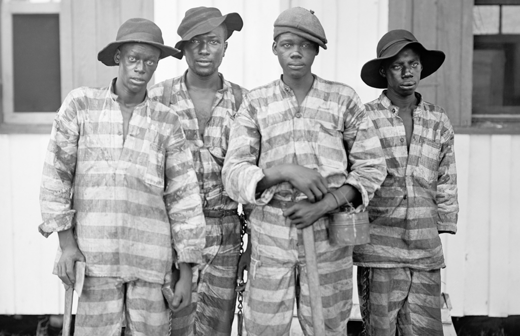 Historic photo of four African American men, part of a prison work crew or what was called a chain gang.