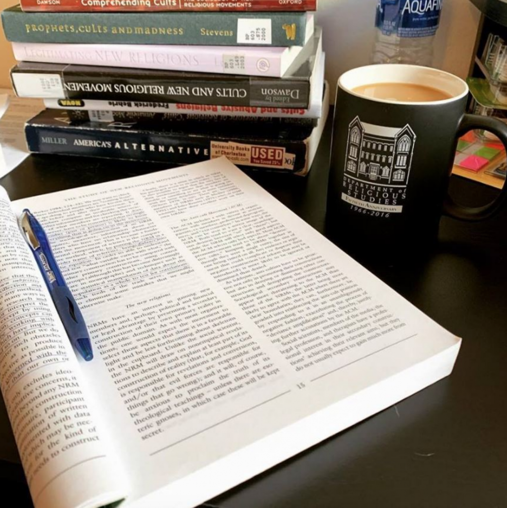 Books and a Department of Religious Studies mug in a library