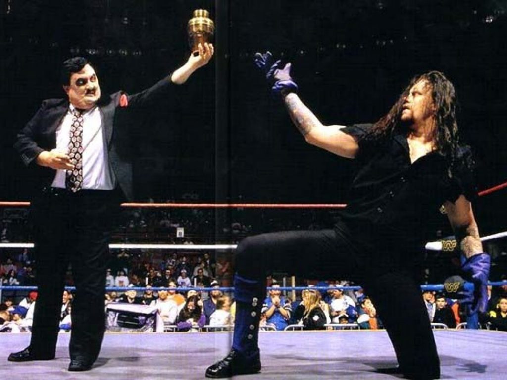 The Undertaker in the wrestlin ring, kneeling.