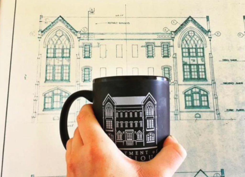 Department mug held up against a background of our building's blueprints
