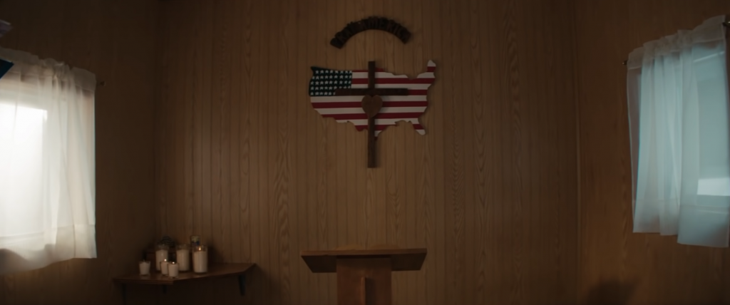 Image from Jeep commercial, of cross and map of America on the wall of a small chapel