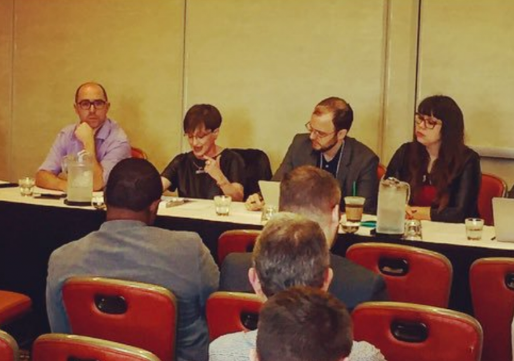 Scholars on a panel presenting their work at a conference