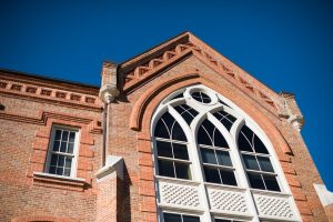 roofline of Manly Hall against a clear blue sky