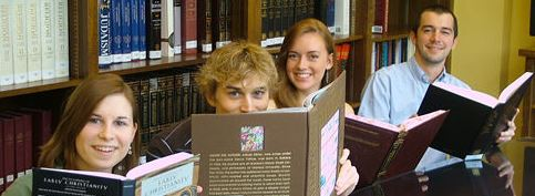 students posing with encyclopedias in the department library