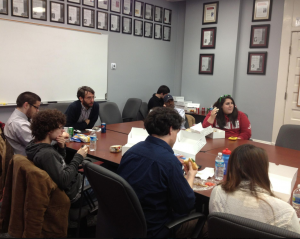 students and faculty enjoy lunch around a discussion table