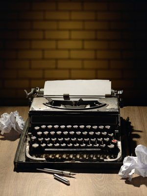 antique typewriter sitting on a desk, surrounded by crumpled sheets of paper