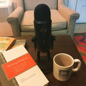 image of microphone, coffee mug, and book on a table