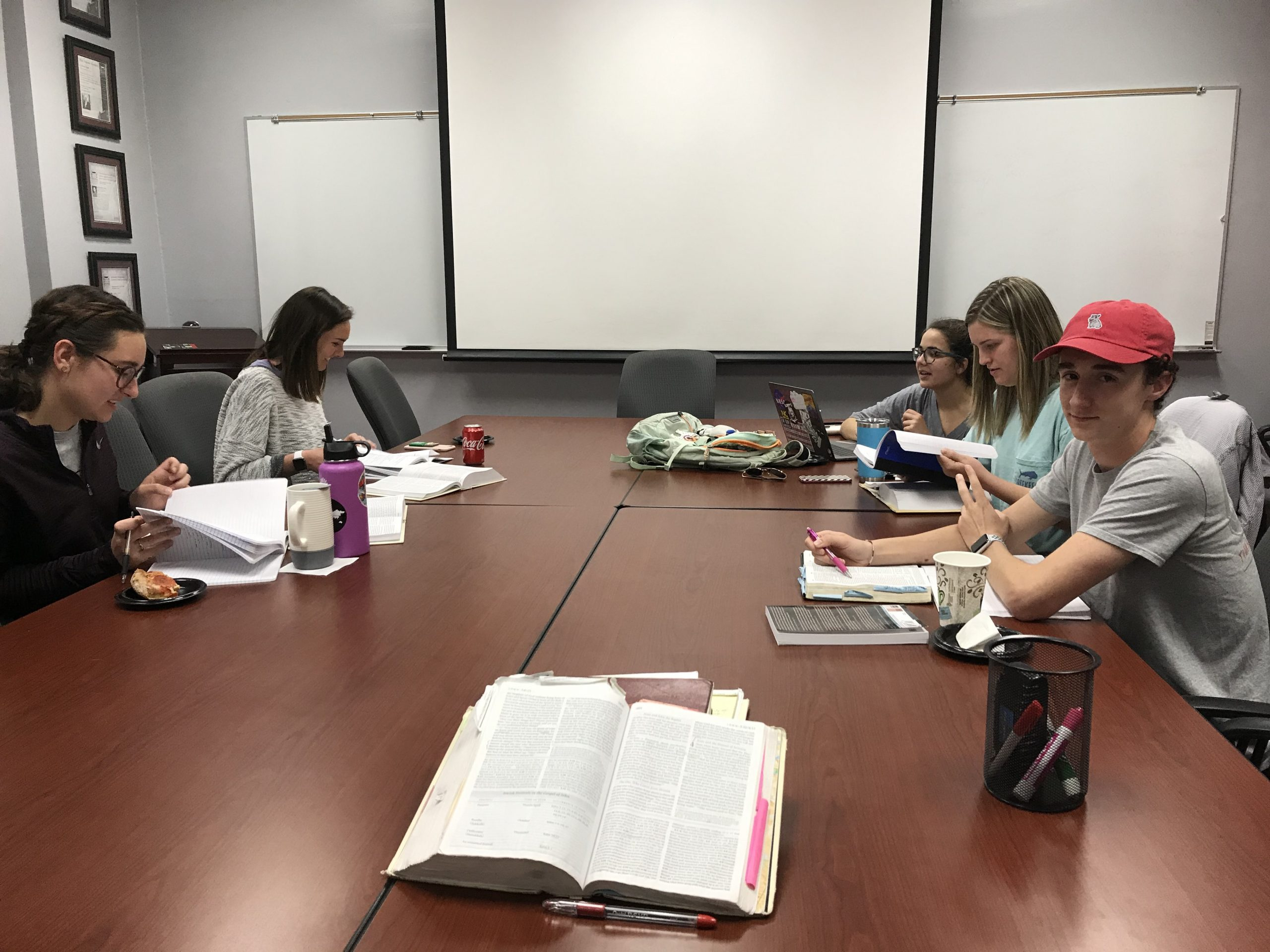 Students reading the Bible and eating pizza in a seminar room.