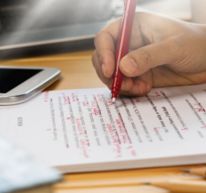 Person copyediting an essay in red pen